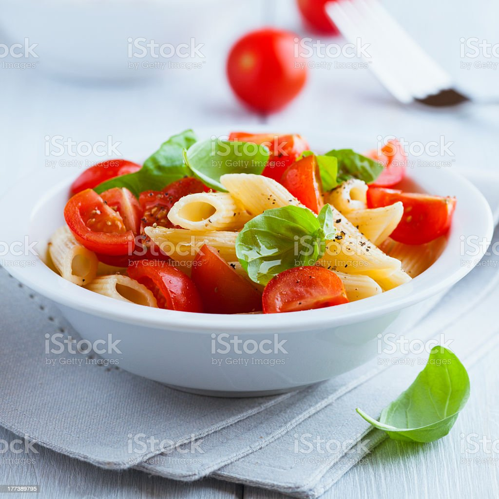 Pasta salad with cherry tomatoes and basil stock photo