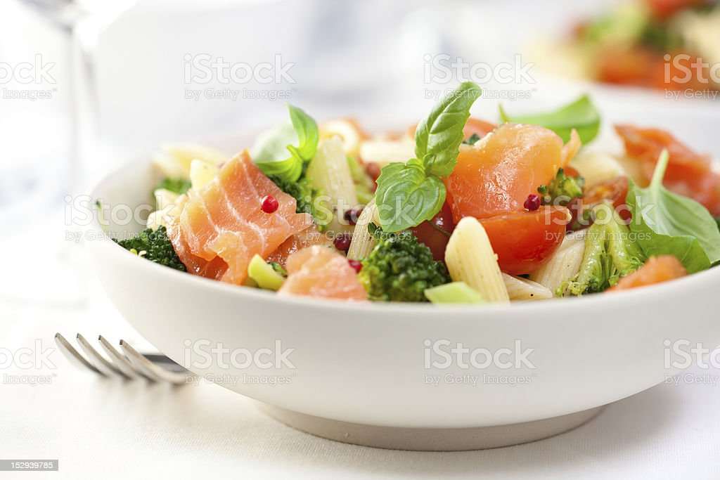 Pasta salad with smoked salmon in a white bowl with a fork stock photo