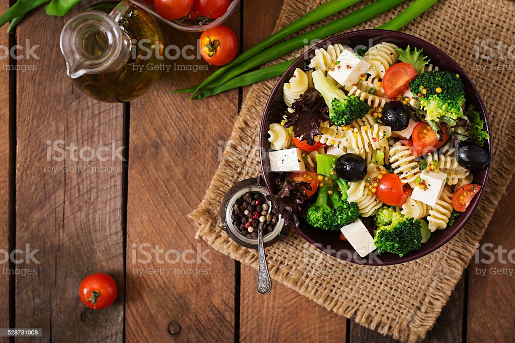 Pasta salad with tomato, broccoli, black olives,  and cheese feta stock photo