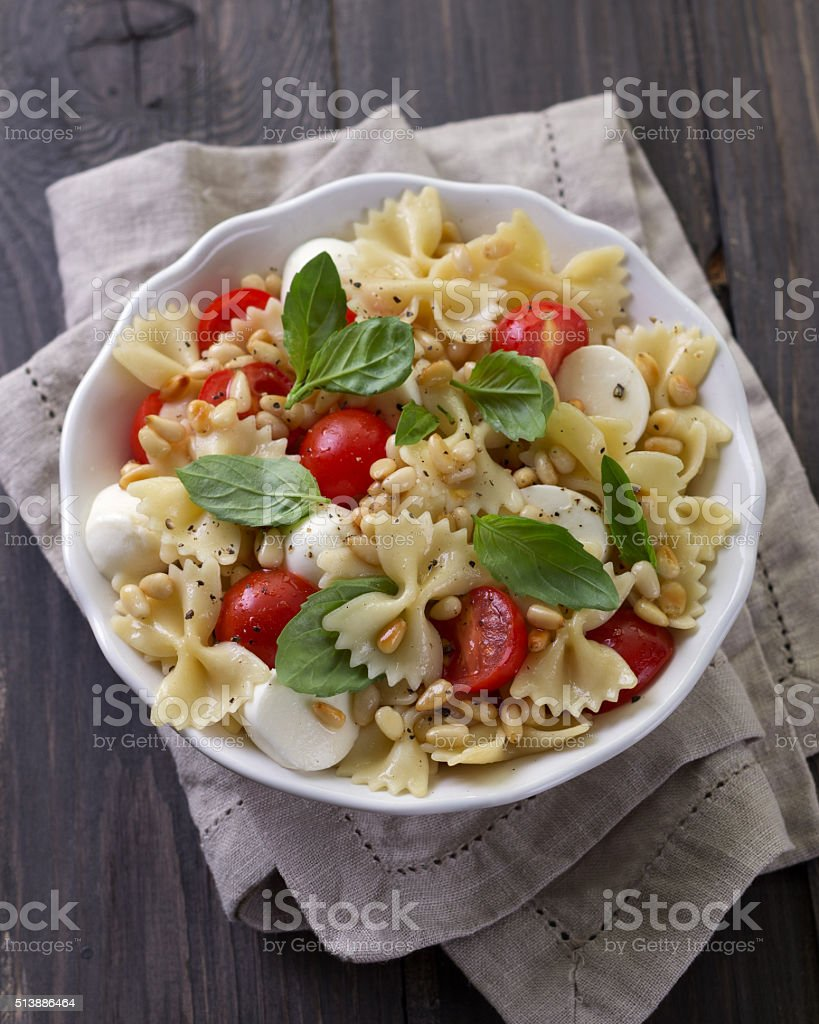 Pasta salad with tomato, mozzarella, pine nuts and basil stock photo