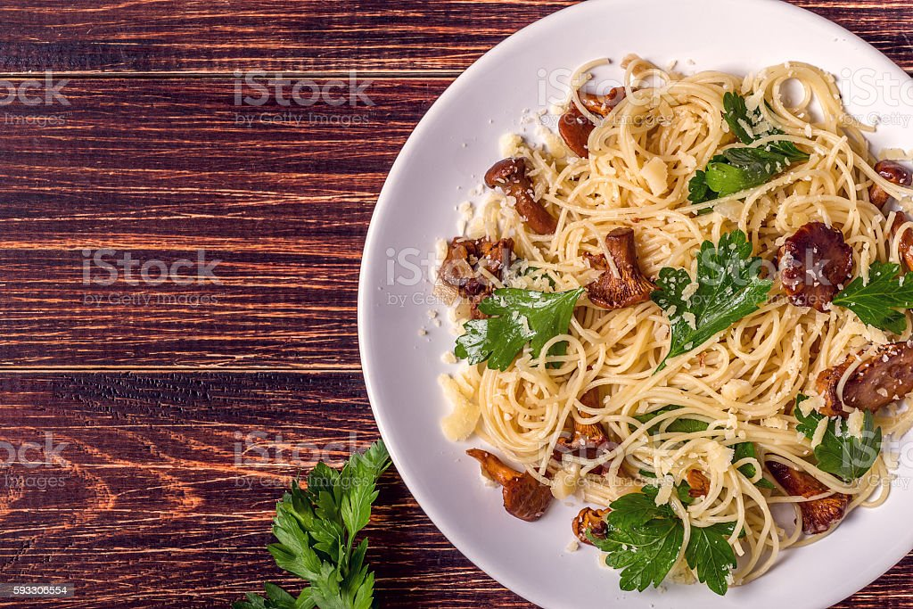 Pasta spaghetti with chanterelles mushrooms on wooden background stock photo