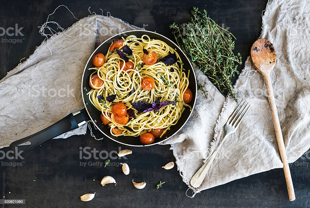 Pasta spaghetti with pesto sauce, basil, cherry-tomatoes, garlic and stock photo