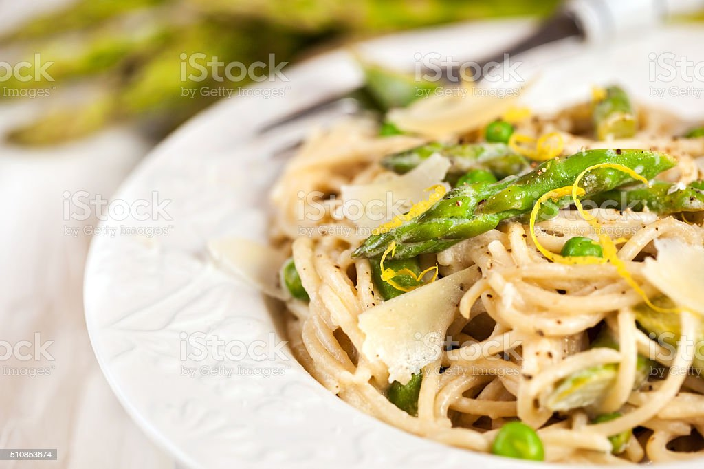 Pasta with asparagus and green peas stock photo