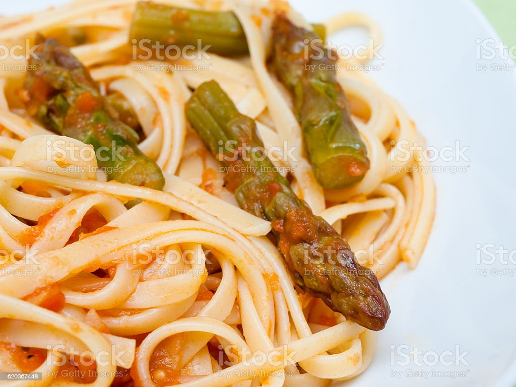 Pasta with asparagus and tomato sauce stock photo