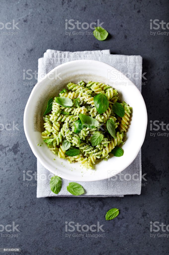 Pasta with basil pesto and fresh basil leaves stock photo