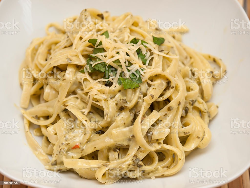 Pasta with basil sauce stock photo