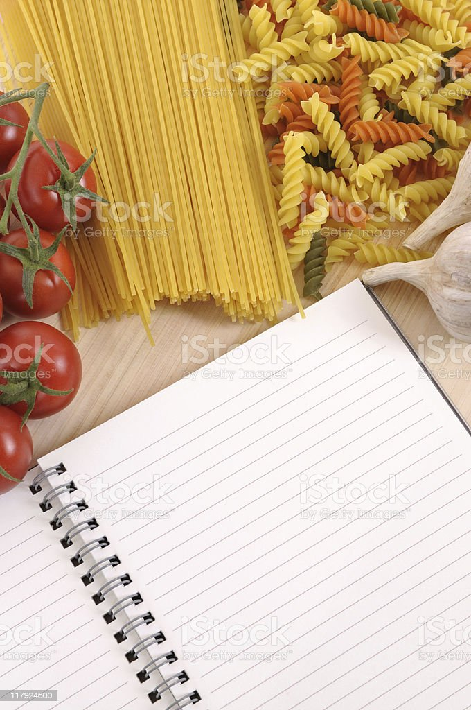 Pasta with blank recipe book and chopping board royalty-free stock photo