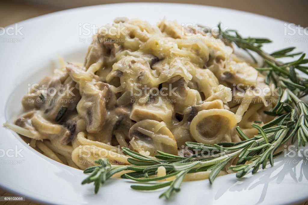 Pasta with creamy sauce, mushrooms and rosemary close up stock photo