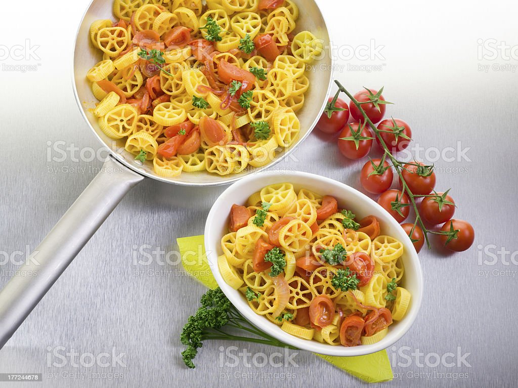 pasta with fresh tomatoes over steel table stock photo
