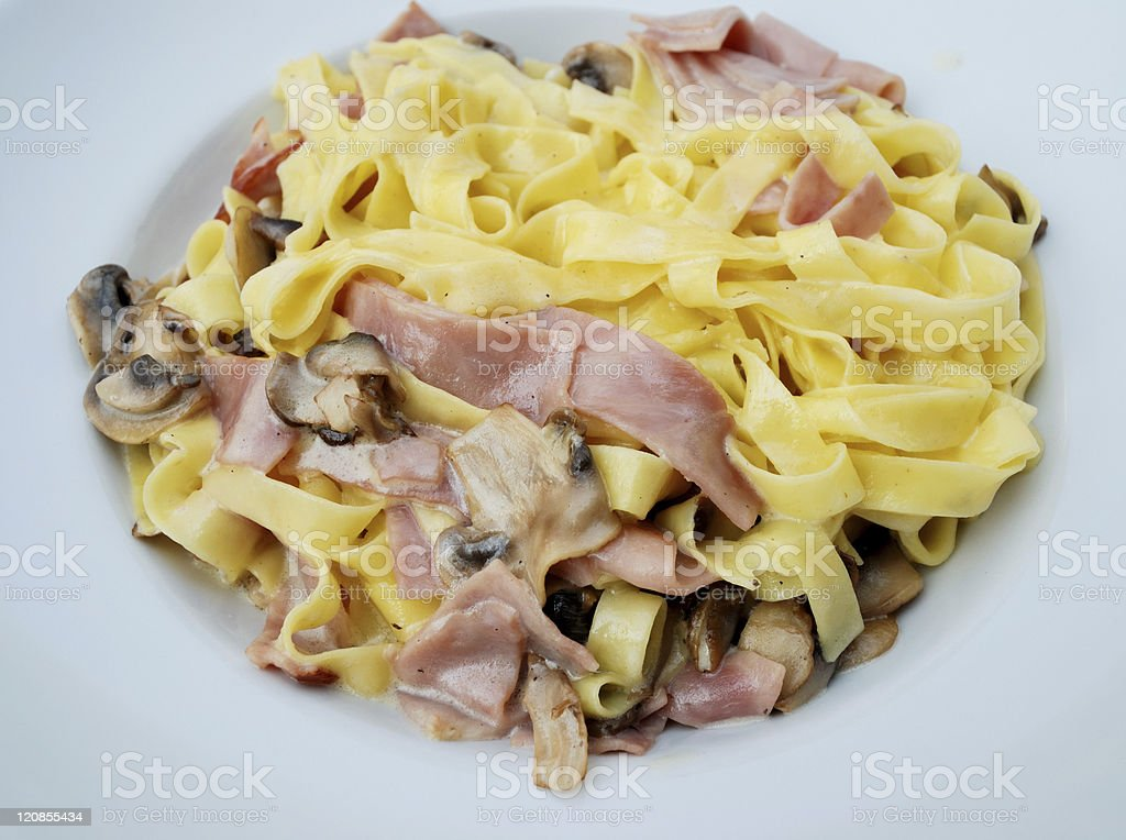 Pasta with ham and mushrooms stock photo