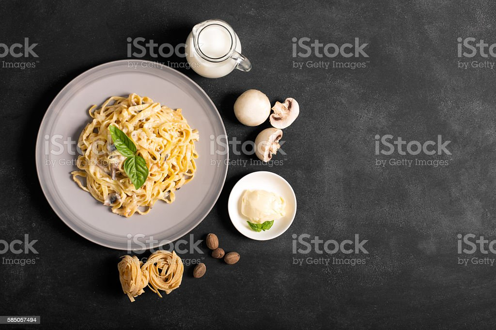 Pasta with mushrooms and bechamel sauce on a black chalkboard stock photo