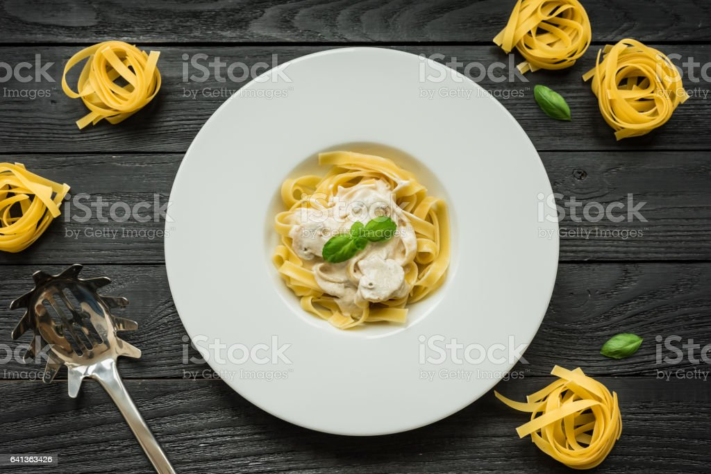 Pasta with mushrooms, basil and cream sauce stock photo