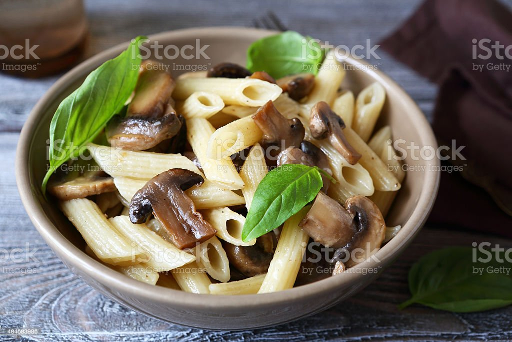 Pasta with mushrooms in a bowl stock photo