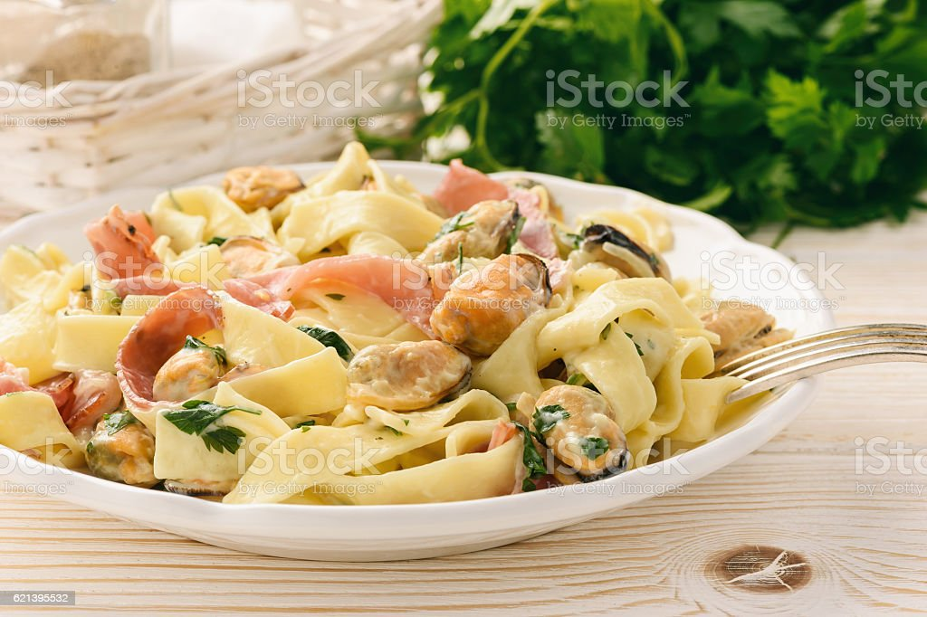 Pasta (pappardelle) with mussels, ham and cheese sauce. stock photo