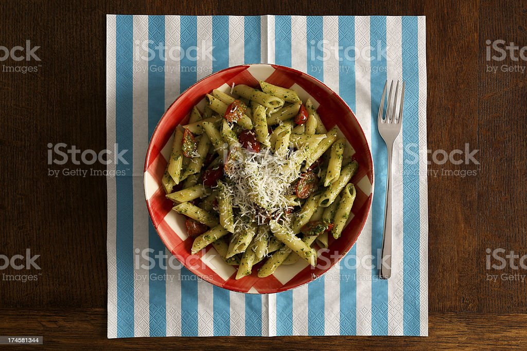 Pasta with pesto sauce, parmesan on gingham plate, turquoise nap royalty-free stock photo