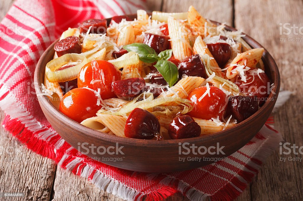 pasta with sausage, leeks, cheese and tomato close up stock photo