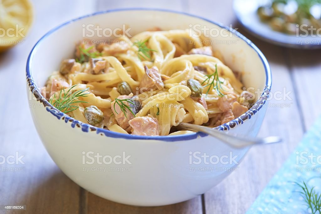 Pasta with smoked salmon and capers in cream sauce stock photo