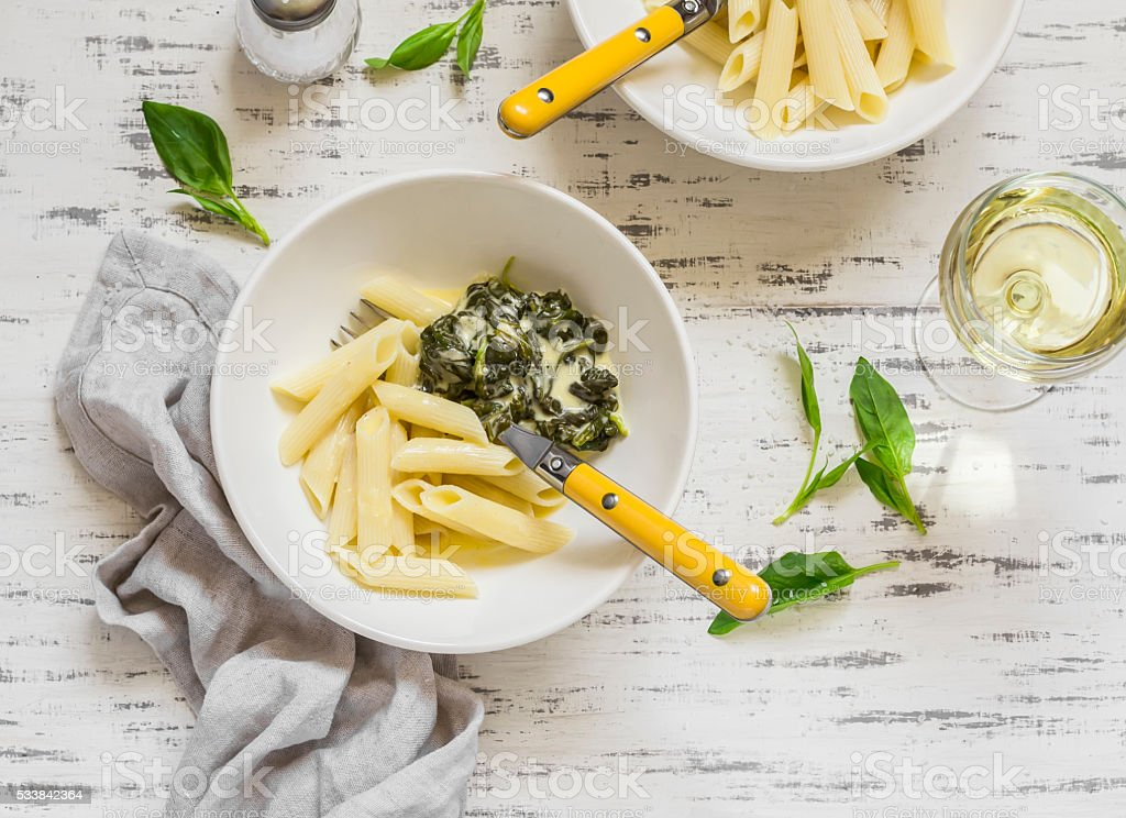 Pasta with spinach cream sauce and  white wine stock photo