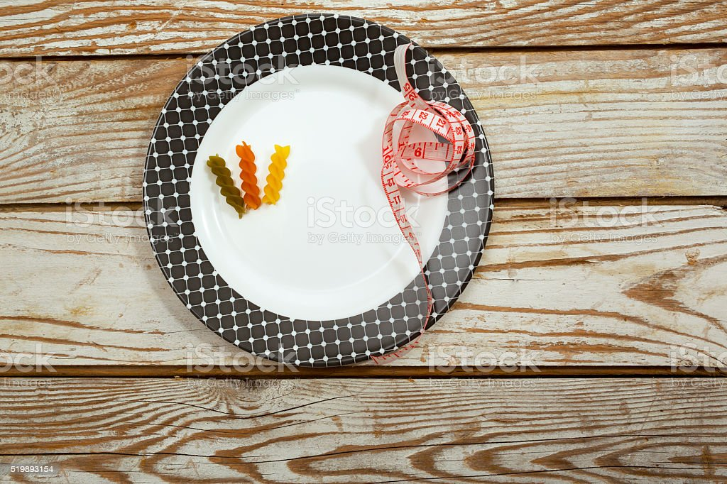 Pasta with tape measure over plate on wooden table stock photo
