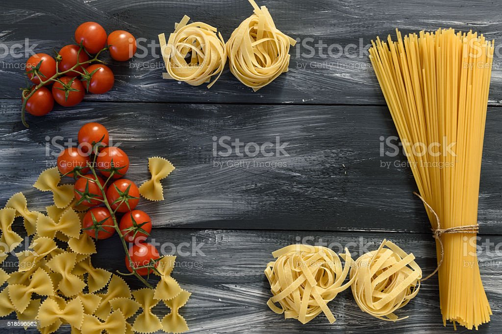 Pasta with tomatoes on wooden background stock photo