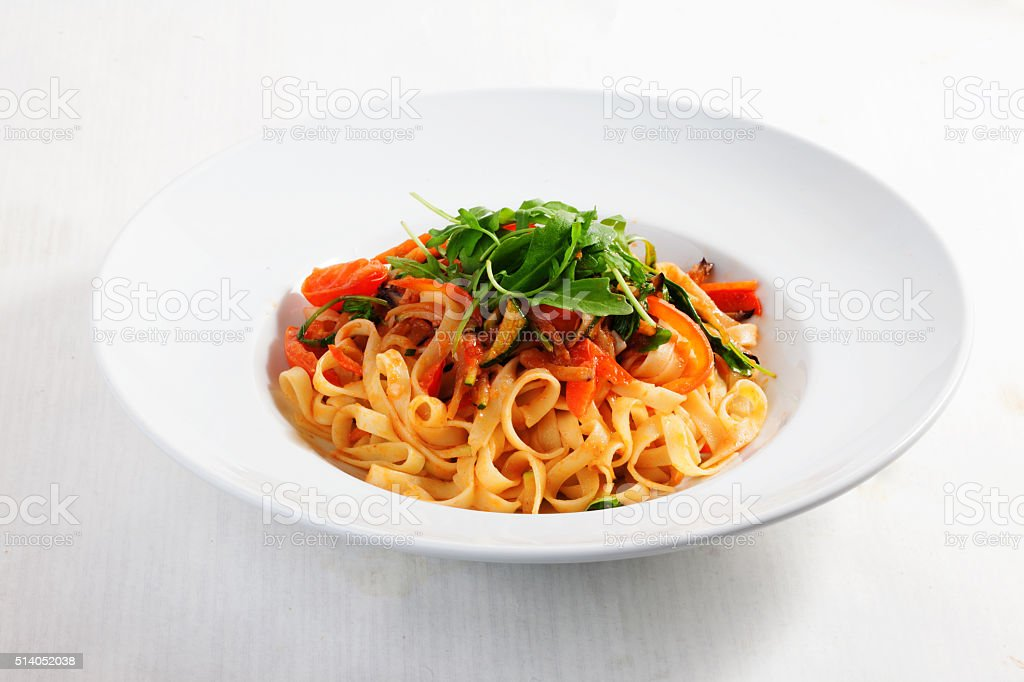 pasta with vegetables, tomatoes, zucchini, peppers, isolated stock photo