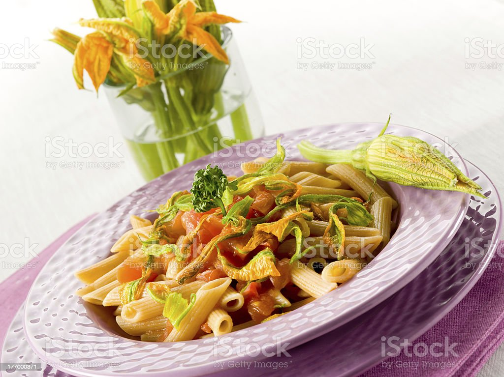 pasta with zucchinis flower and fresh tomatoes stock photo