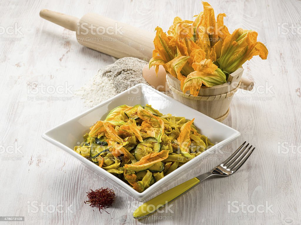 pasta with zucchinis flower and saffron stock photo