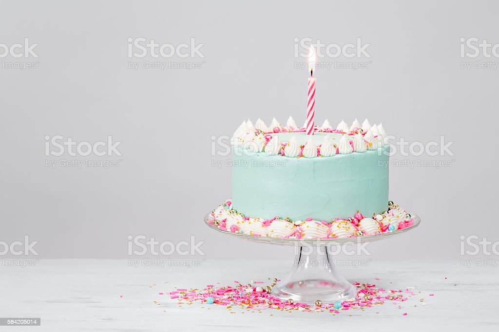 Pastel blue birthday cake over white background with pink sprinkles.