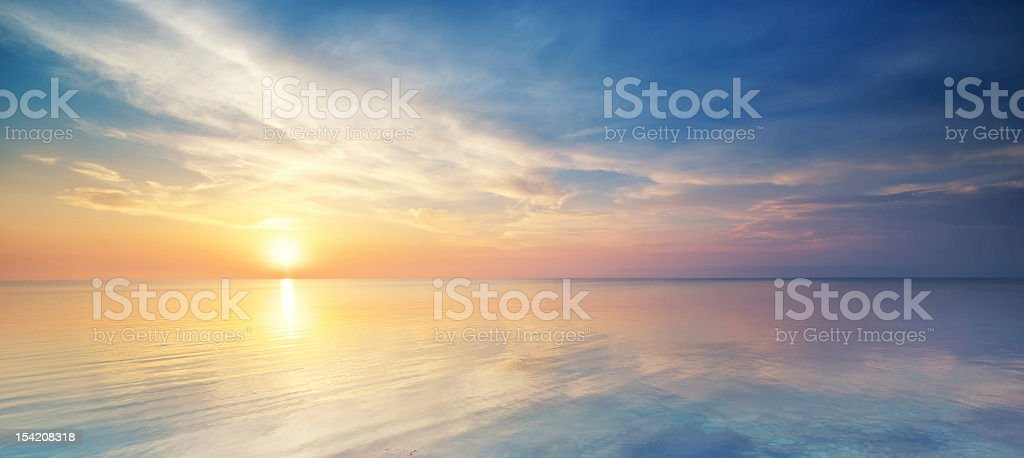 Pastel sunset over the ocean in a cloudy sky stock photo