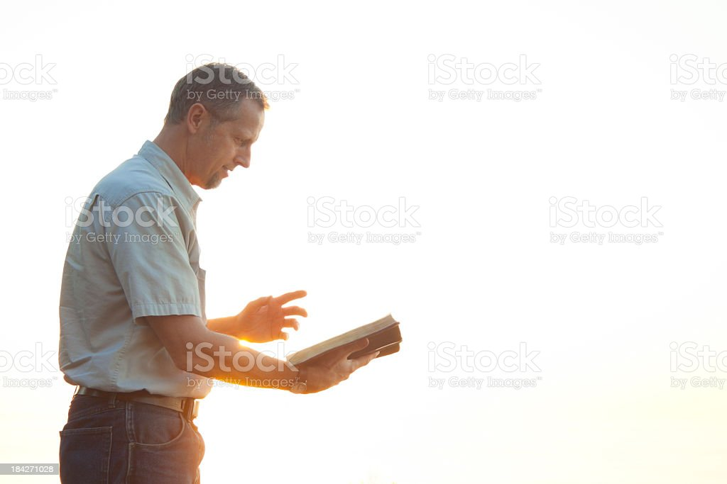 Pastor casually dressed walking in sunlight reading Bible stock photo