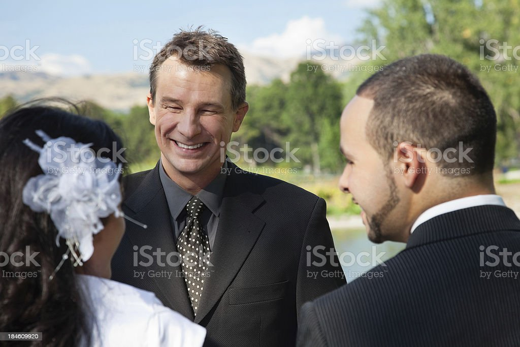 Pastor officiating an outdoor wedding stock photo