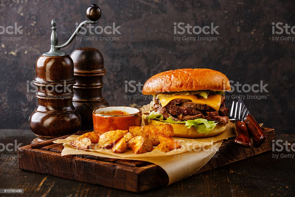 Pastrami Burger with sliced Roast beef and potato wedges stock photo