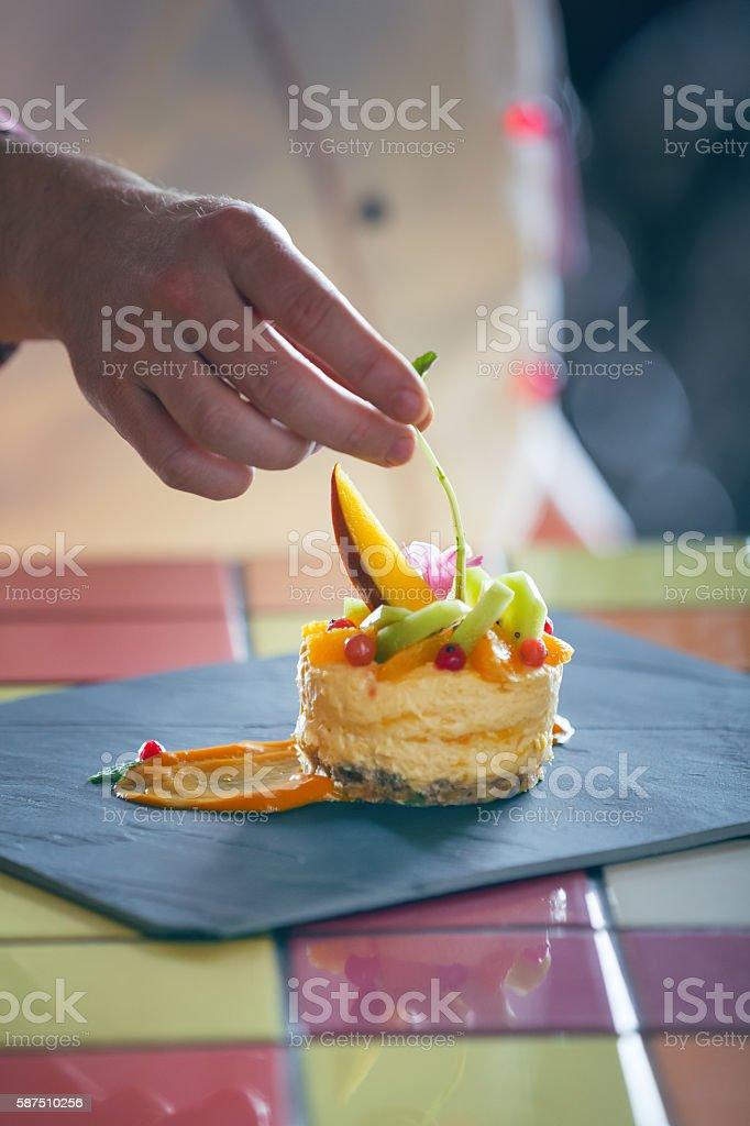 Pastry chef garnishing mango mousse cake stock photo