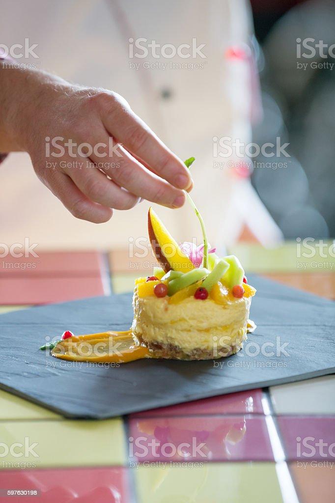 Pastry chef garnishing mousse cake stock photo