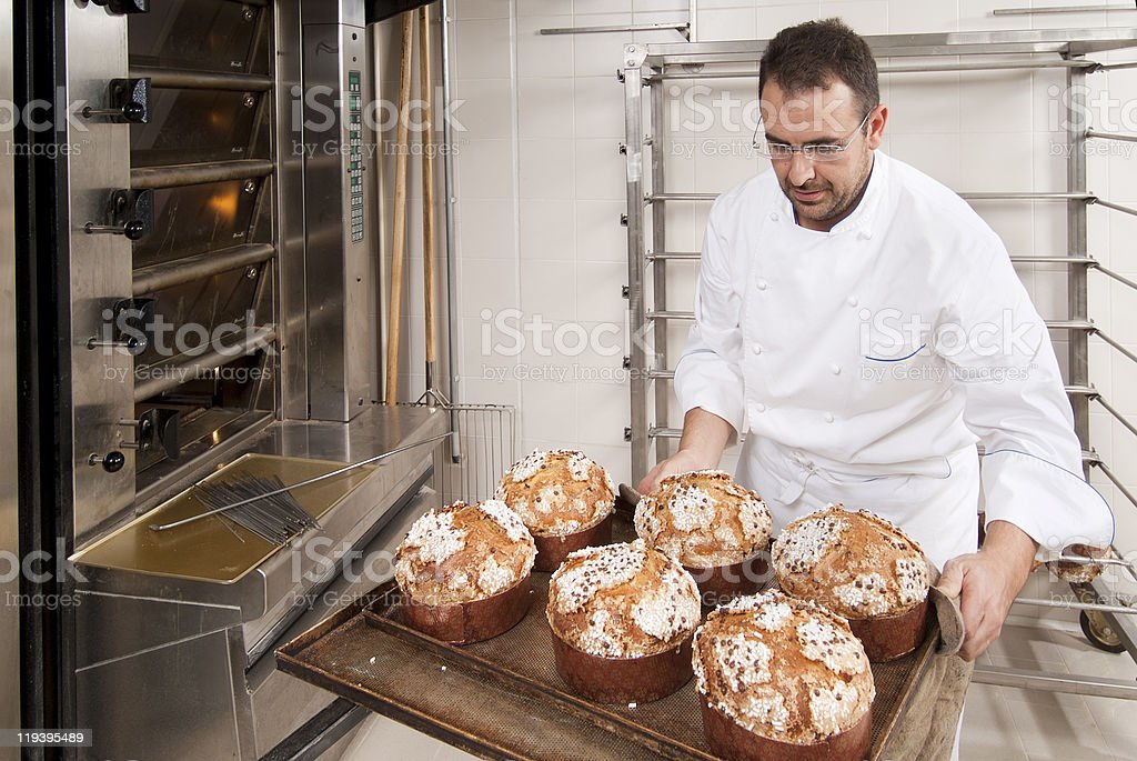 Pastry chef putting some cakes in the oven royalty-free stock photo