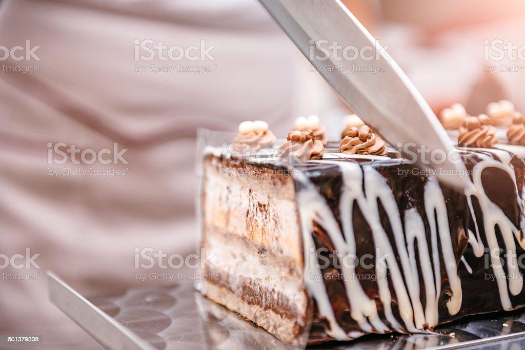 Pastry chef taking slice of cake stock photo