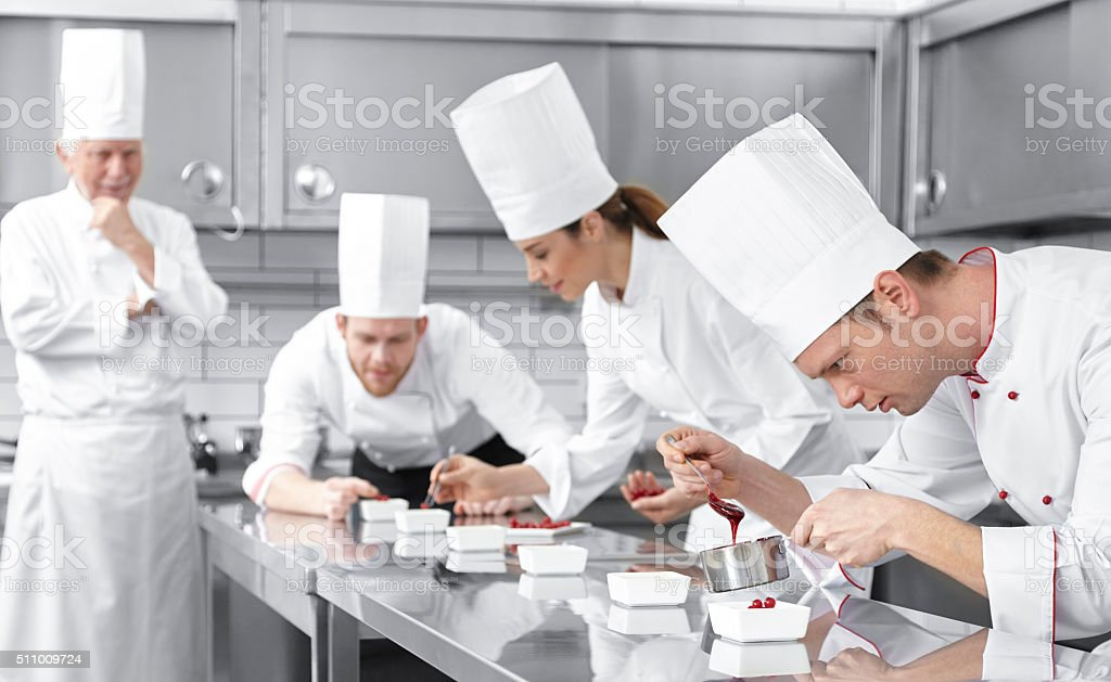 Pastry chefs decorating desserts stock photo