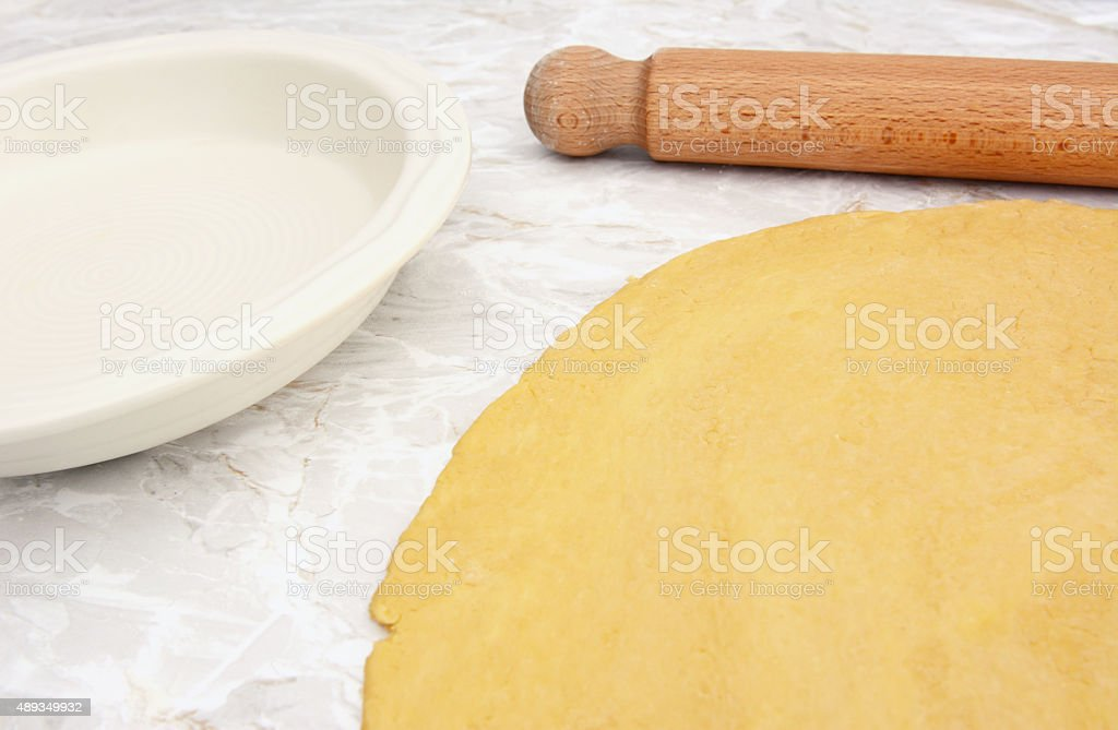 Pastry rolled out with rolling pin next to pie dish stock photo