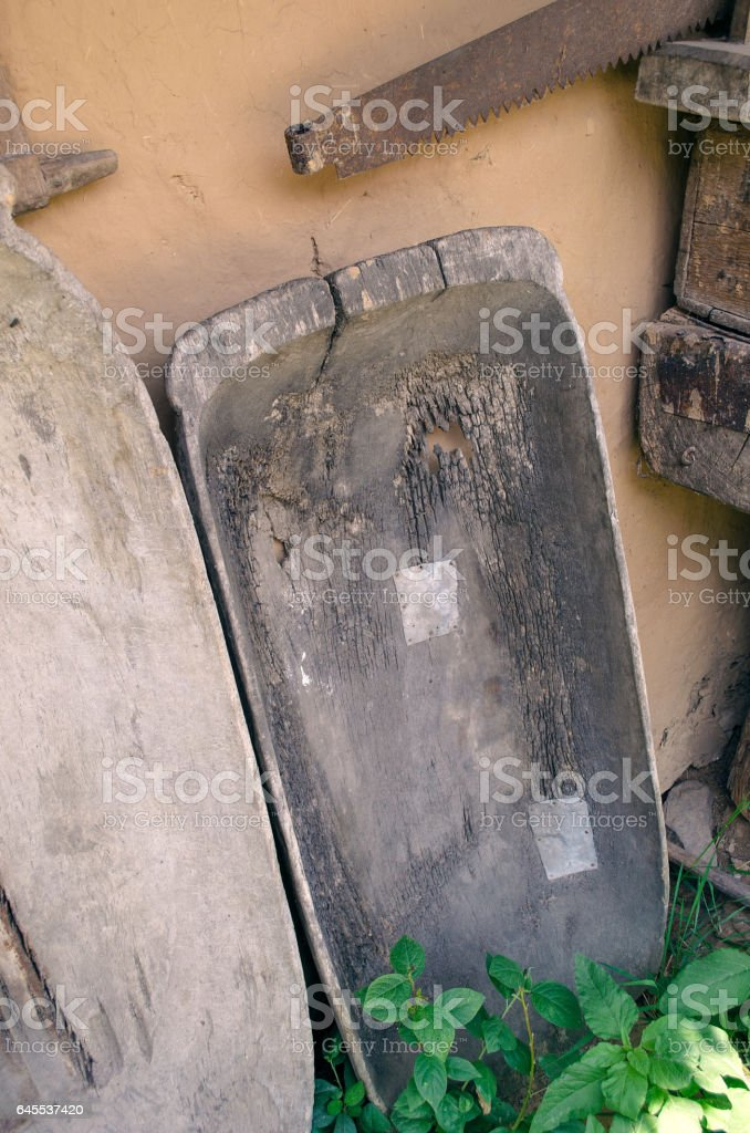 Patched old wooden trough with a hole and rusty saw stock photo