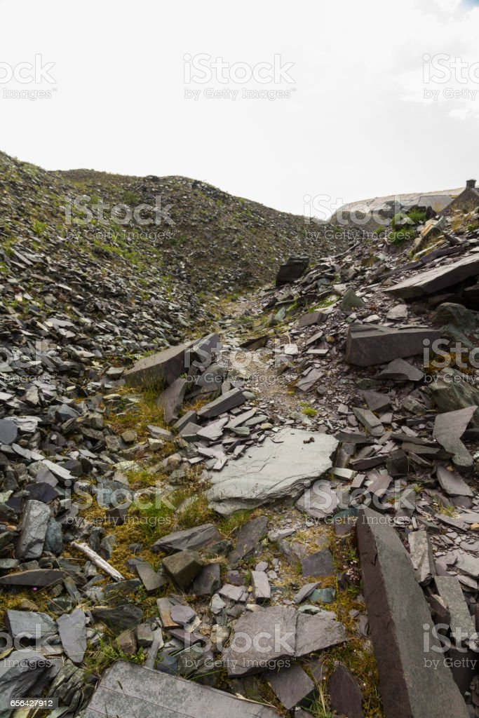 Path between old slate spoil heaps stock photo