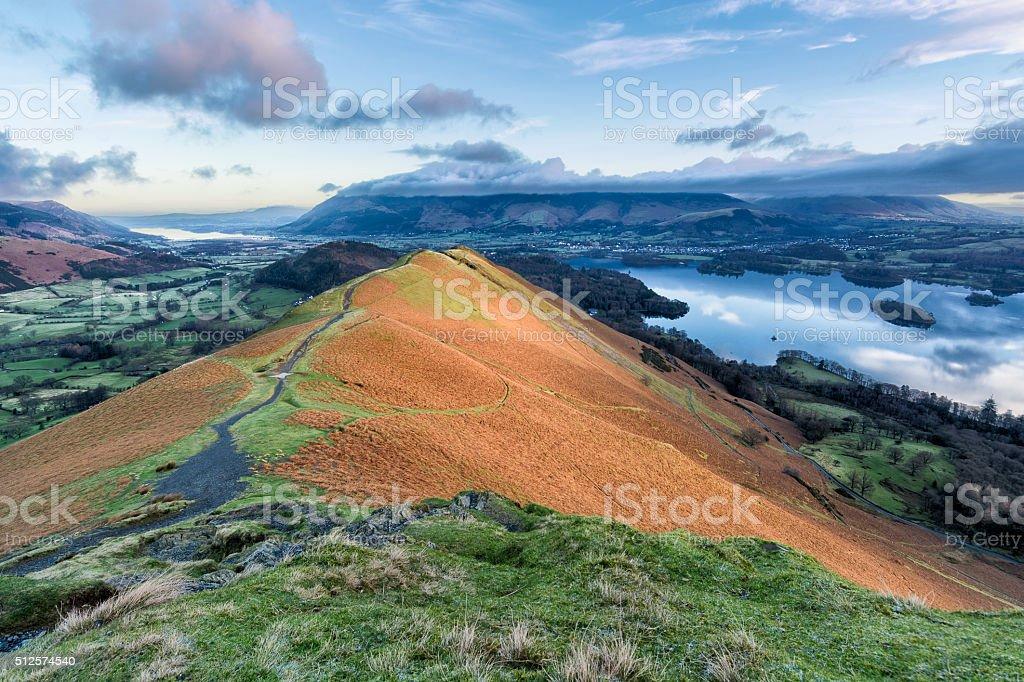 Path Leading Along Mountain Ridge With Lake And Cloudy Sky. stock photo