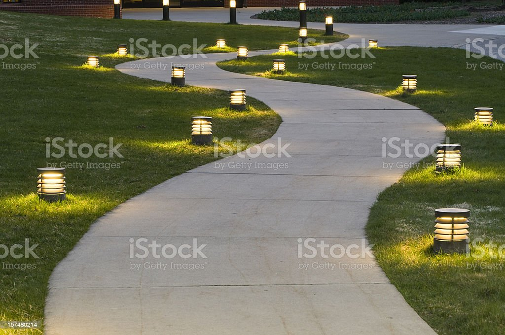 A path through the grass lit by lanterns stock photo