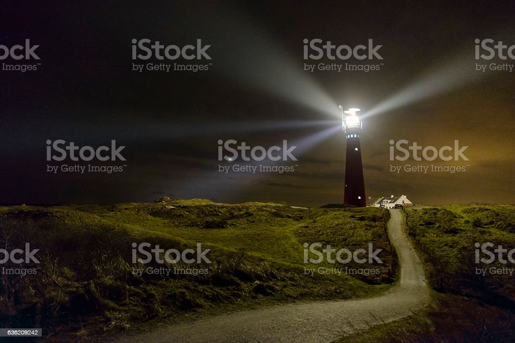 Path to the lighthouse in the dunes at night stock photo