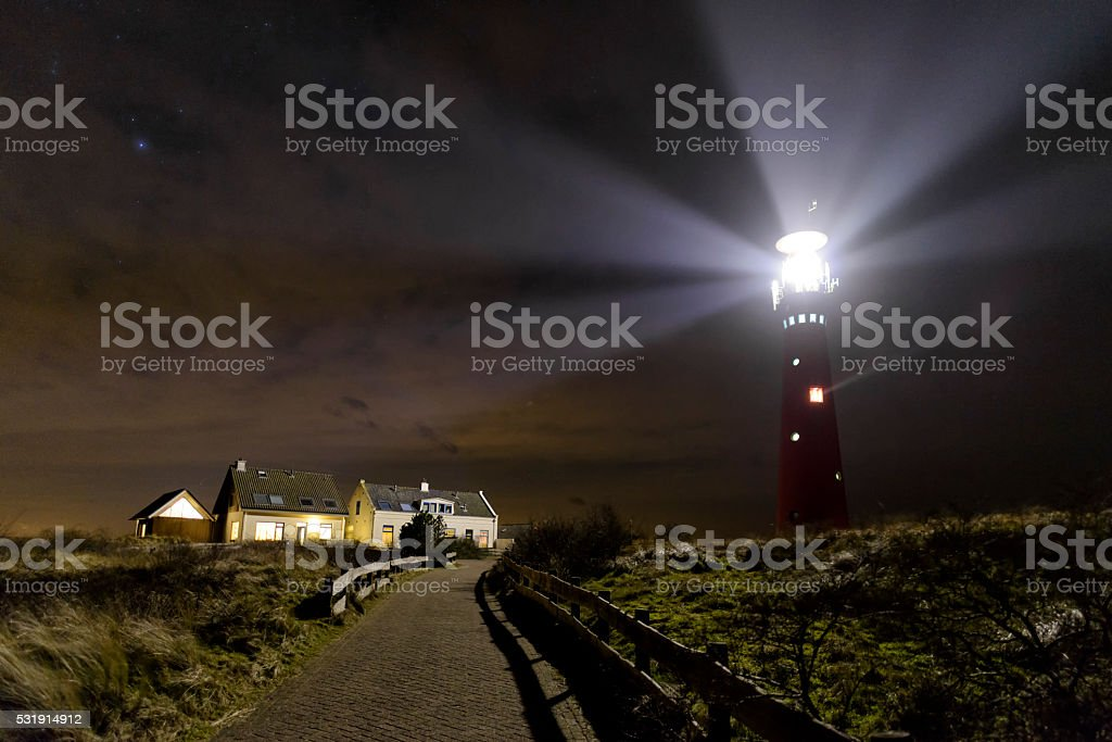 Path to the lighthouse in the dunes stock photo