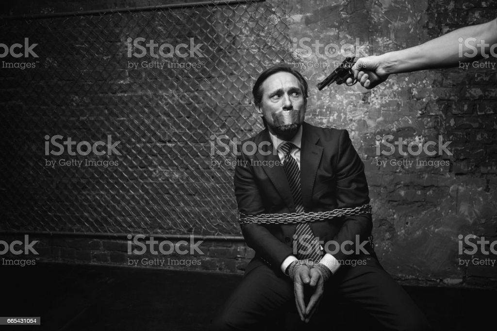 Pathetic broken businessman afraid of his kidnapper stock photo