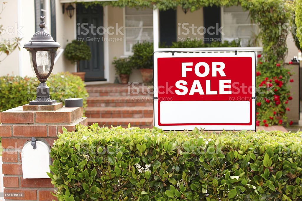 Pathway to a house that has a for sale sign stock photo