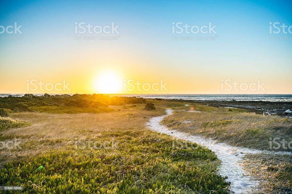 Pathway to sunset at Kommetjie beach stock photo