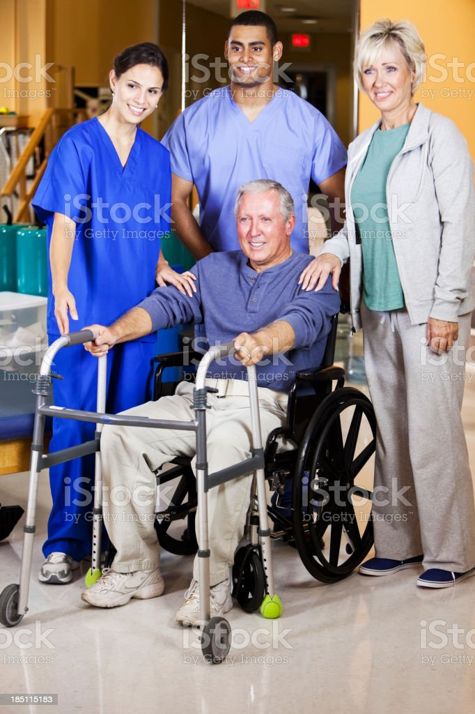 Patient and spouse with healthcare workers stock photo
