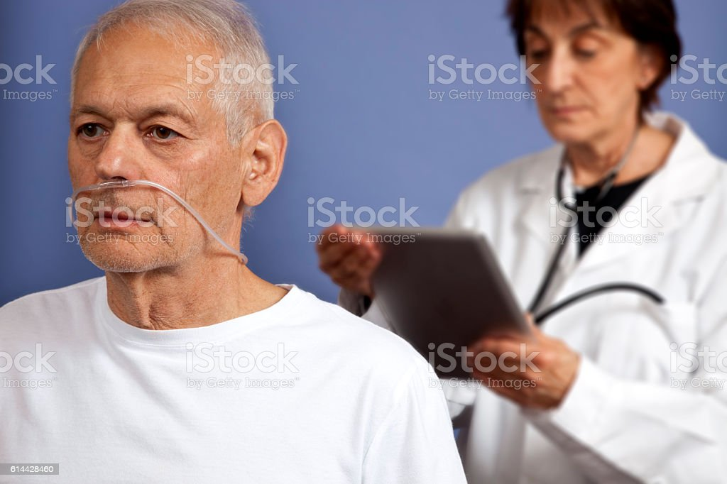 Patient awaiting news from doctor standing behind patient stock photo