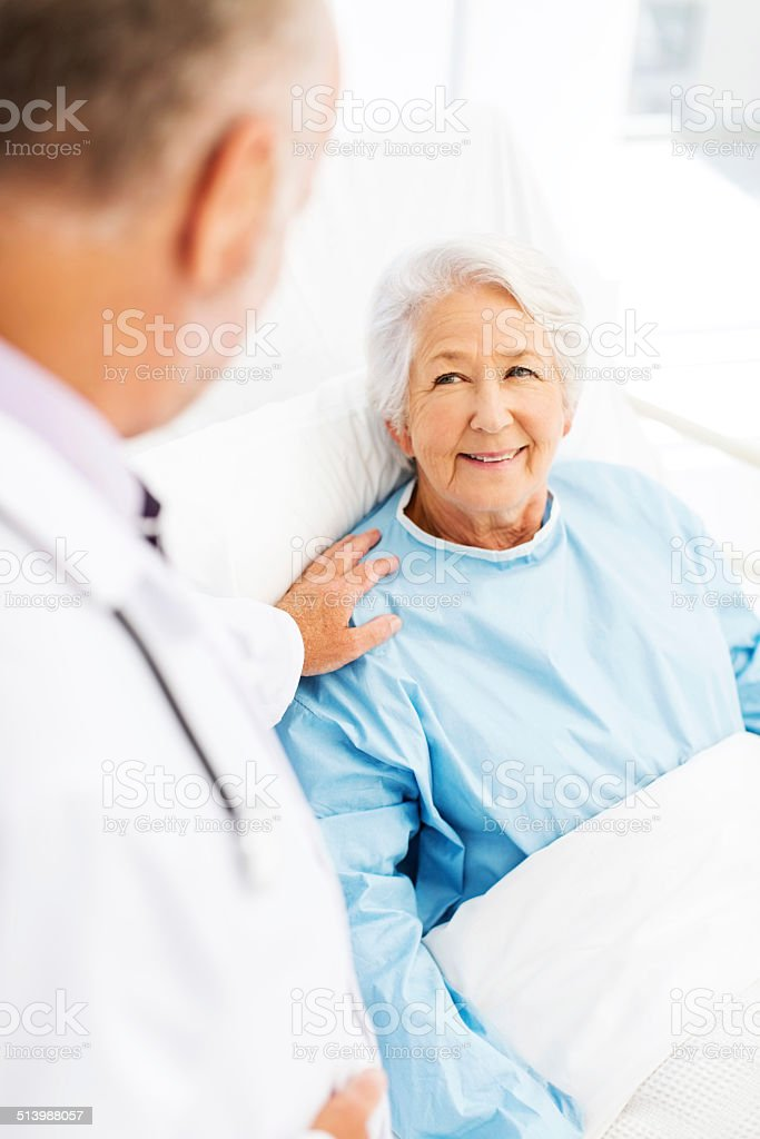 Patient Being Console By Doctor In Hospital Ward stock photo